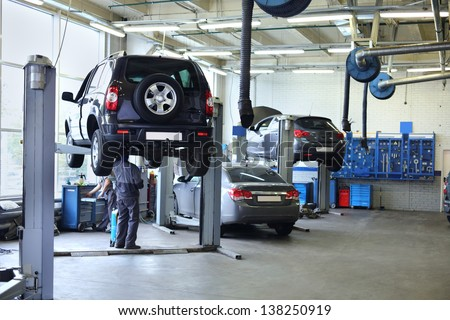 Three black cars stand in small service station and two men repair one car. - stock photo