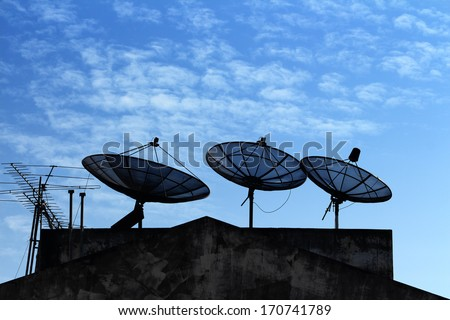Three black satellite dish on building roof with cloudy blue sky background