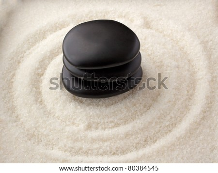 Three black stones in a pile, over circles of white sand - stock photo