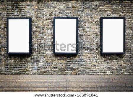 three blank billboards attached to a building exterior old brick wall - stock photo