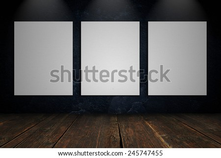 Three blank canvas on a concrete wall - stock photo