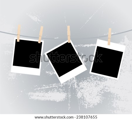 Three blank instant photos hanging on the clothesline.