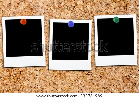 Three blank polaroids affixed on cork board with colorful small thumb tack - stock photo
