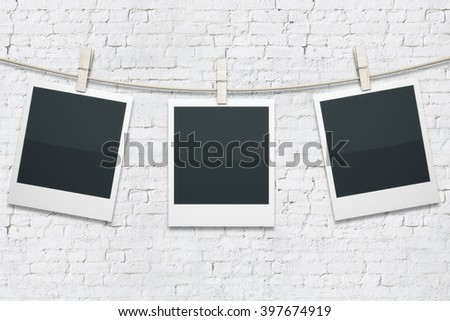 Three blank polaroids hanging on rope with clothespins on white brick background. Mock up - stock photo