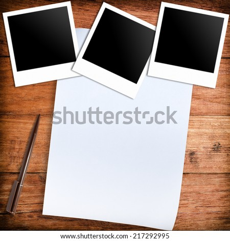 three blank retro polaroid photo frames and white paper and pen over wooden background - stock photo