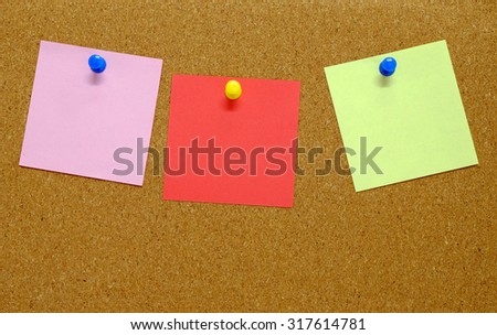 three blank sticky notes on corkboard background