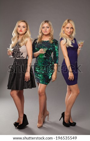 three blonde girls wearing evening dresses drinking martini over grey background - stock photo
