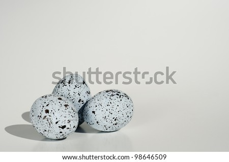 three blue eggs with black spots bunched in a group and isolated on white background - stock photo
