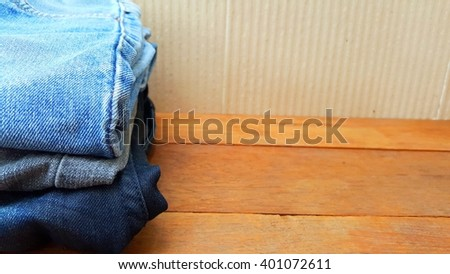 Three  blue jeans on wooden board. Color jeans fashion.