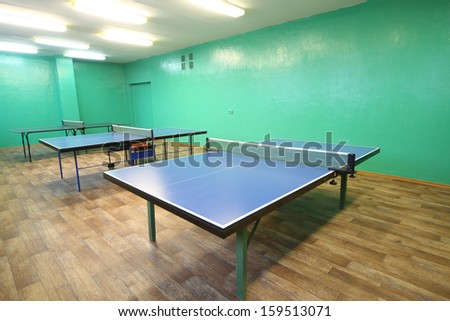 Three blue ping pong tables in the room with green walls - stock photo
