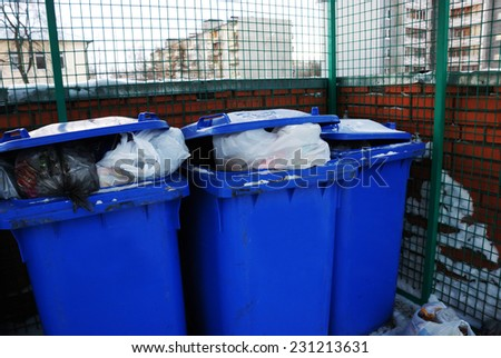 three blue plastic garbage can in yard - stock photo