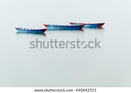 Three blue small boats on Phewa Lake in Pokhara, Nepal - stock photo