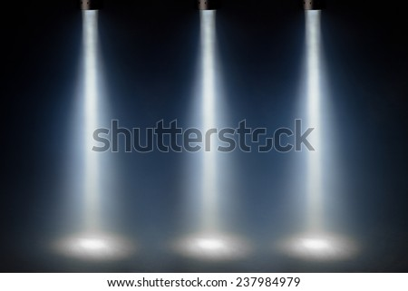 three blue spot lights on stage - stock photo