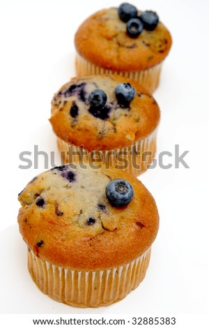 Three blueberry muffins with fresh berries on top on a light colored background - stock photo