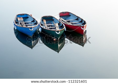 Three boats on clear water with the only reflections coming from the boats.  Each boat is painted a different colour: Red, Green & Blue. - stock photo