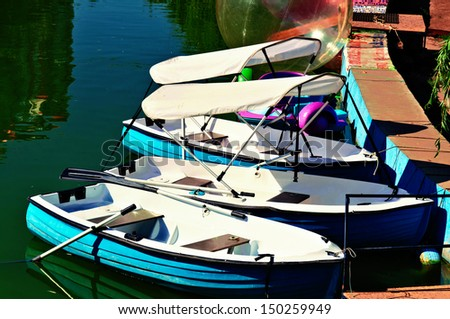 Three boats on the water in the pond. - stock photo