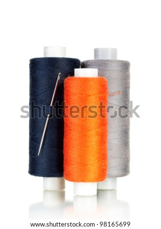 three bobbin thread with needle and sewing pin isolated on white - stock photo