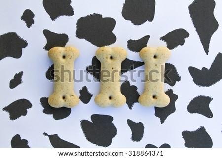 Three bone shaped dog shaped dog biscuits on animal skin background - stock photo