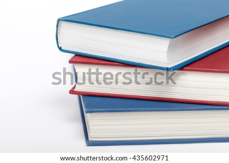 Three books on white background up close. Low aperture shot, selective focus. - stock photo