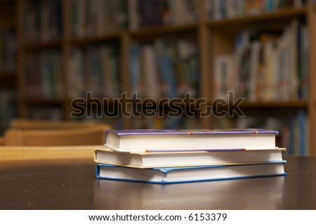 three books stacked on a table - stock photo