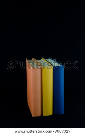Three books,with orange, yellow and blue spines, lined up in a row. Isolated against black background. - stock photo
