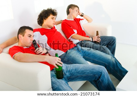 Three bored men sitting on couch and watching TV. - stock photo