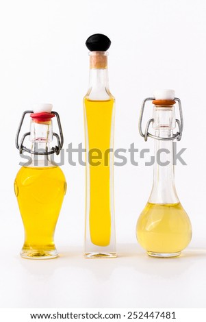 three bottles of bright olive oil on white background