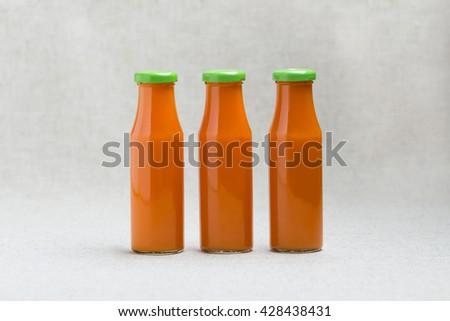 Three bottles of carrot juice. Selective focus. - stock photo