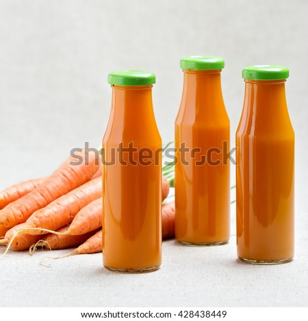 Three bottles of carrot juice with carrots. Selective focus. - stock photo
