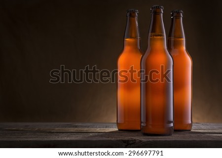 Three Bottles of Cold Beer on a Rustic Wooden Table - stock photo