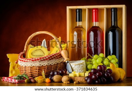 Three bottles of wine with basket cheese, grapes and food in still life