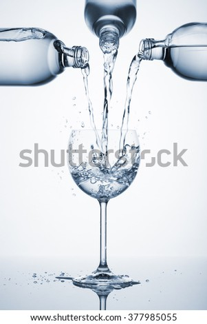 three bottles pouring water in glass with splashes, with blue light - stock photo