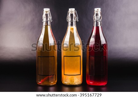 Three bottles with drinks of different colors on a black background - stock photo
