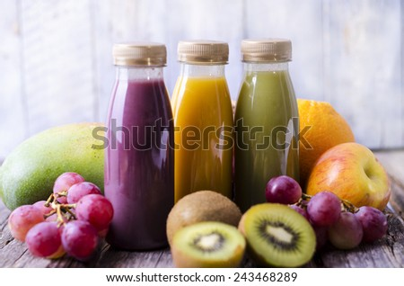 Three bottles with smoothies and fresh fruit (apple, grapes, kiwifruit, mango) - stock photo