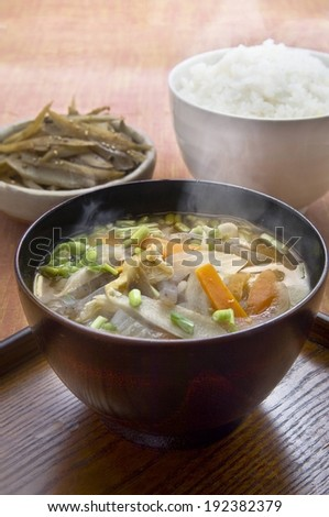 Three bowls on a table, one of which contains a vegetable broth. - stock photo