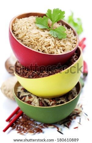 Three bowls with different types of rice on white background - stock photo