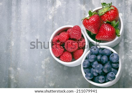Three bowls with summer berries like strawberries, raspberries, blueberries  - stock photo