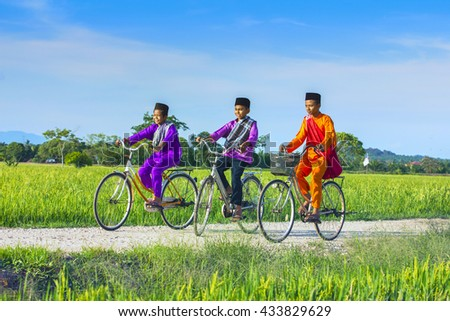 three boy cycling in paddy field during blue sky - stock photo