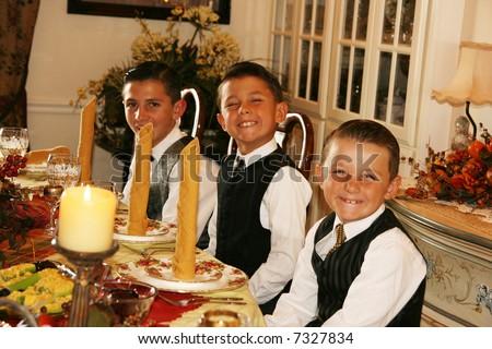 three boys all dressed up for a formal family dinner in the dining room - stock photo