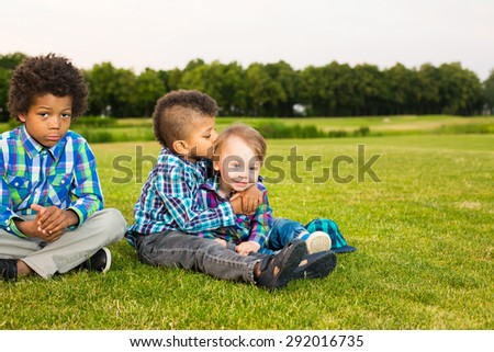 Three boys are sitting on the evening glade and playing.