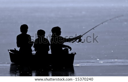 Three boys fishing from a boat in silhouette. - stock photo