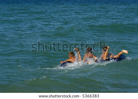 Three boys float on an inflatable mattress on the sea