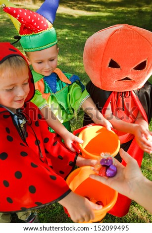 Three boys in halloween costumes are getting their candies - stock photo