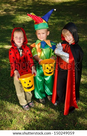 Three boys in halloween costumes are waiting for candies