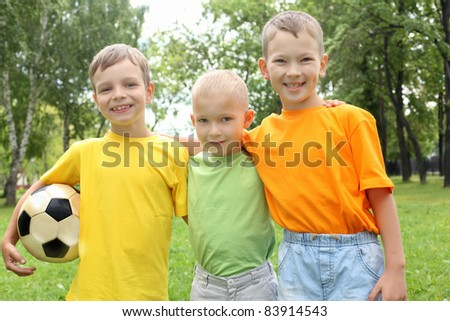 Three boys in the park with a ball - stock photo