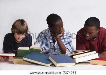 Three boys laying on the floor reading