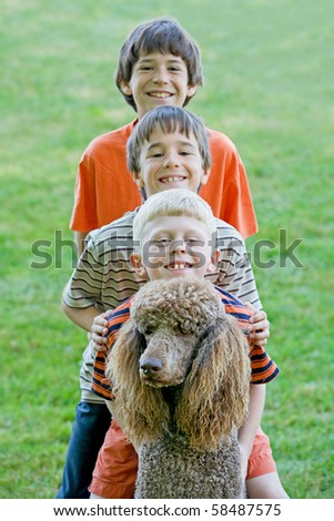 Three Boys Playing With Their Dog - stock photo