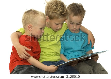 Three boys reading a book, holding each other.