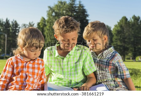 Three boys reading an interesting book in the park - stock photo
