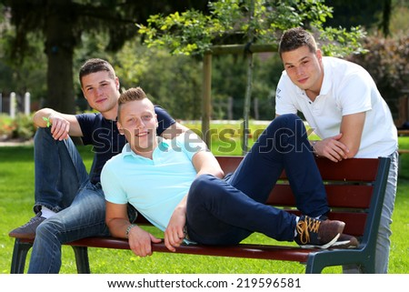 Three boys sitting on a bench in a park